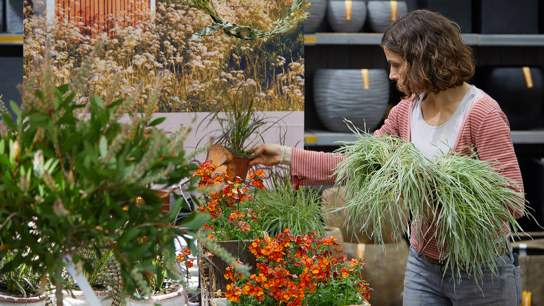 Stefanie Thierfelder places grasses and plants in the shop