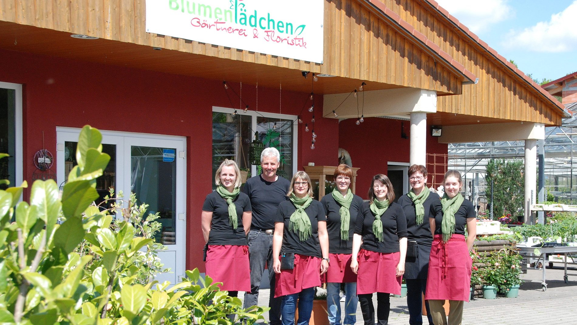 Owner Elmar Fleck with members of his family company in front of the Blumenlädchen Morles